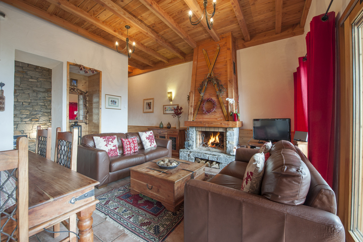 The living area is complete with comfortable leather sofas and cosy log fire.